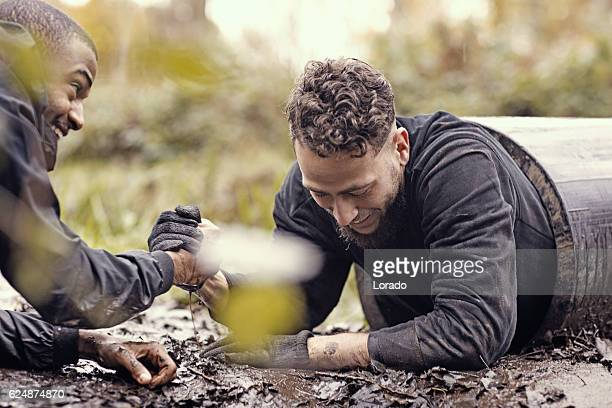 Caucasian young man being helped from tunnel during obstacle course