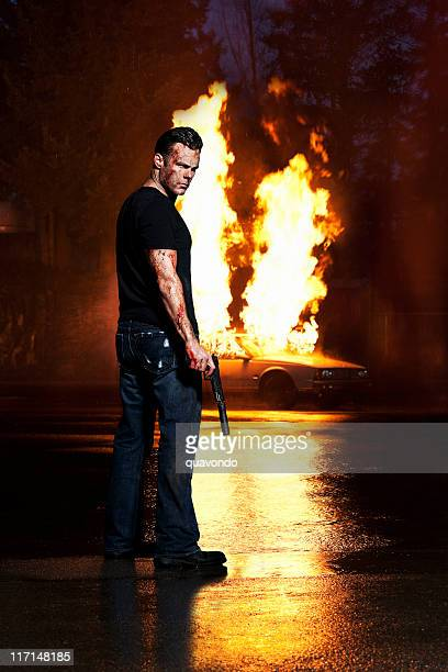 Angry, Bloody Man Holding Gun, Posing with Car on Fire
