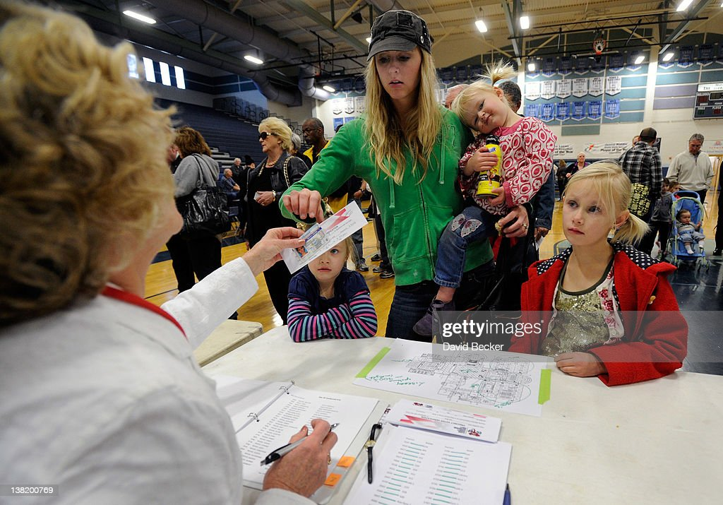 A caucus worker checks in Katherine Wood with her three daughters (L-R) Ellie Wood, Reese Wood and Ashlyn Wood before the start of the Republican caucus at Centennial High School on February 4, 2012 in Las Vegas, Nevada. Nevada is the first state in the West to vote as Republicans go about choosing their presidential candidate.