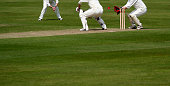Focus on Cricket Ball which nicks Bat as Wicket Keeper is about to catch out Batsman,with plenty or room for Text