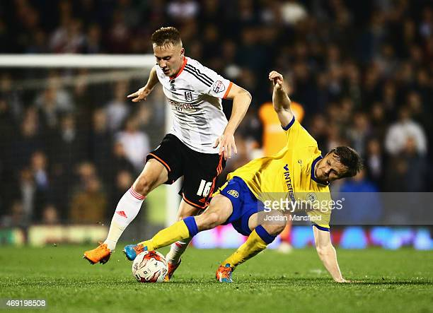 Cauley Woodrow of Fulham is challenged by William Kvist of Wigan Athletic during the Sky Bet Championship match between Fulham and Wigan Athletic at...