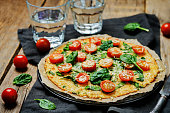 Cauliflower pizza crust with tomato and spinach. toning. selective focus
