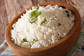 Cauliflower rice with basil close up in a bowl on the table. horizontal