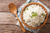 Cauliflower rice with basil close up in a bowl on the table. horizontal top view
