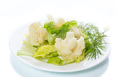 cauliflower with salad leaves on white background