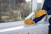 construction worker caulking window frame with silicone sealant
