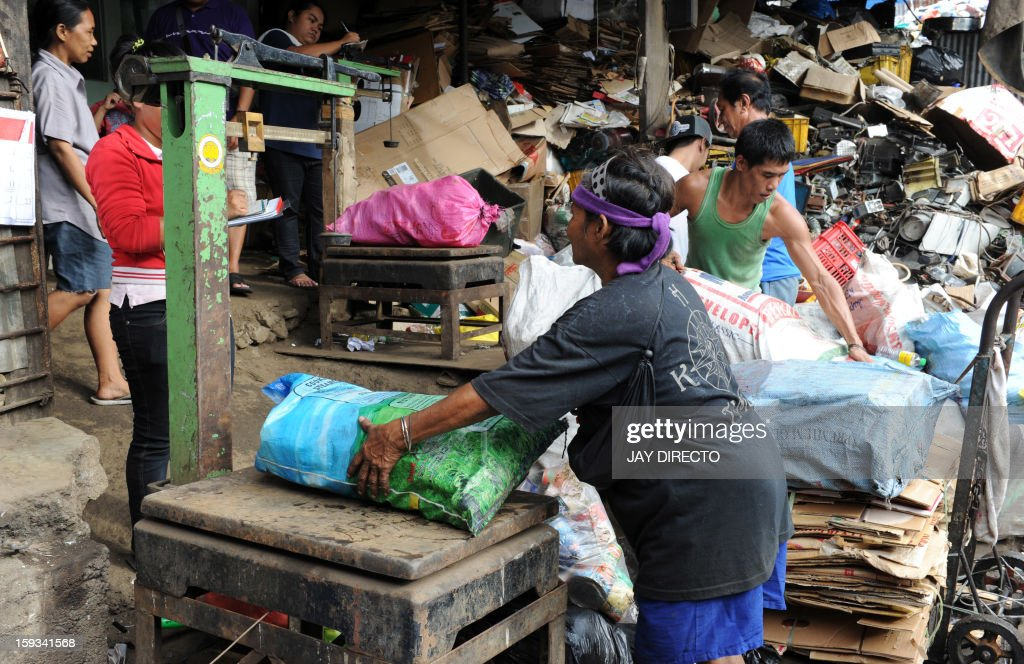 Caustomers sell garbage to a junkshop in Manila on January 12, 2013. The shop buys different kinds of recyclable materials from metal to papers and plastics which are used to make new materials. AFP PHOTO / Jay DIRECTO