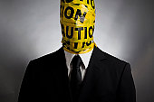 Image of  man in a suit wrapped in caution tape