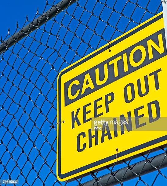 Caution Keep Out sign on fence
