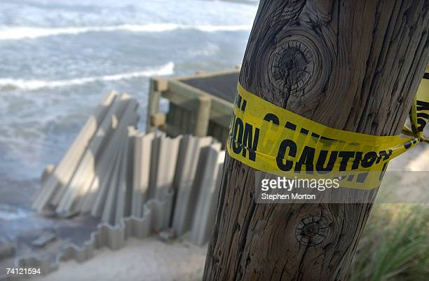 Caution tape is wraped around a pole to warn people of the 20 foot dropoff after waves from Subtropical Storm Andrea eroded portions of this beach...