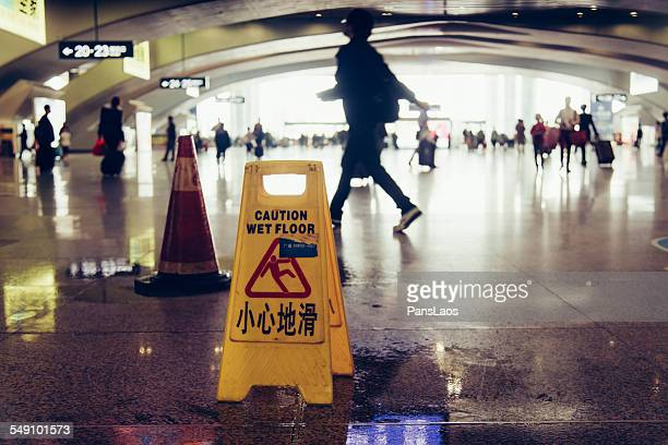 Caution wet floor sign with blur busy people