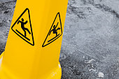 Caution wet floor, yellow warning sign stands on gray asphalt urban ground, close up photo