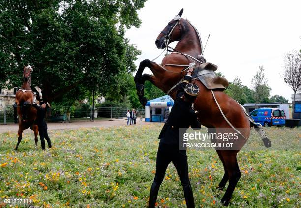 Cavaliers du Cadre noir de Saumur control horses at the 'BiodiversiTerre' garden near to the Arc de Triomphe on June 3 2017 in Paris A farm and its...