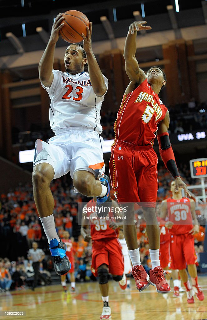 Cavaliers forward Mike Scott left heads toward the basket against Terrapins guard Nick Faust right on a long breakaway pass as the University of...
