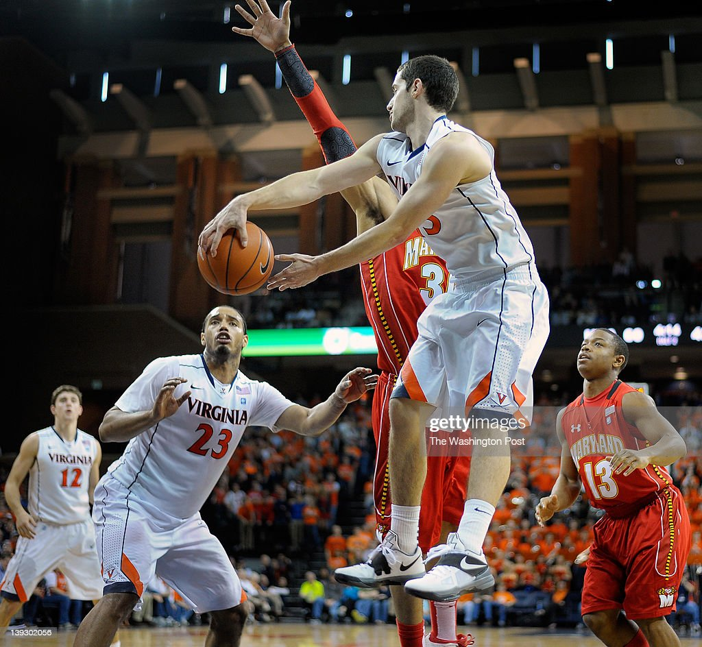 Cavaliers guard Sammy Zeglinski 2nd right dishes off under the basket to teammate Mike Scott 2nd left during the University of Virginia defeat of the...