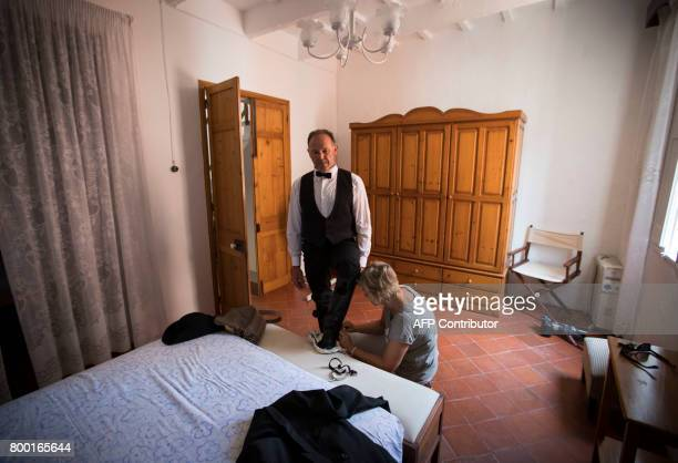'Cavaller' Toni Galmes is helped by his wife Maria to get prepared before the traditional San Juan festival in the town of Ciutadella on the Balearic...