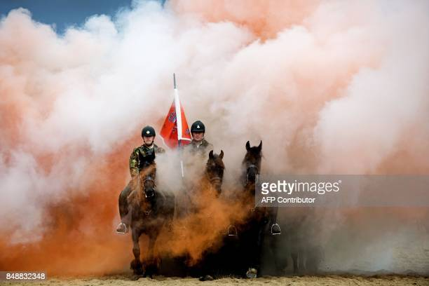 Cavalry horses and their riders are exposed to smoke as members of the Dutch cavalry undergo a stress test at the beach in Scheveningen on September...