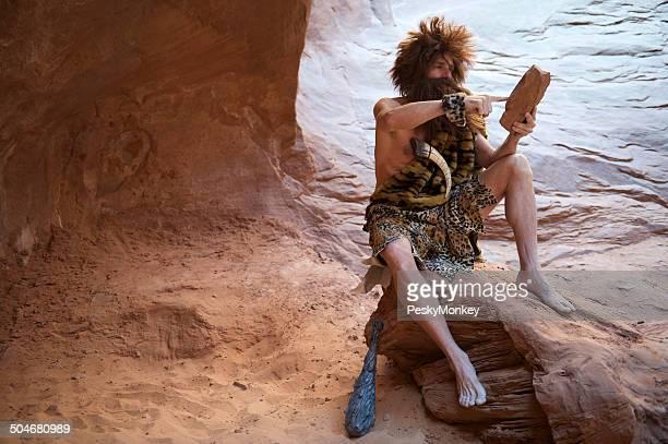 Homem das Cavernas sentado ao ar livre com pedra Tablet com ecrã táctil
