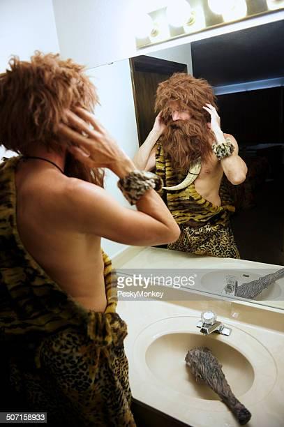 Caveman parado en espejo de aseo baño para hombres