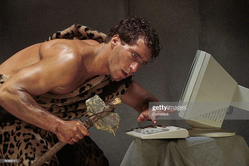 Caveman with computer : Stock Photo