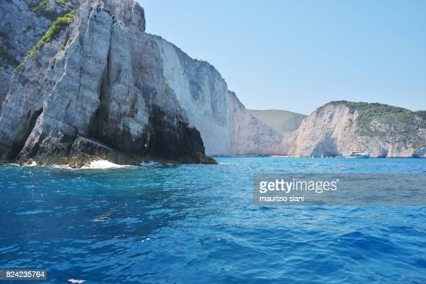 Caves By Blue Sea Against Sky And Famous Navagio shipwreck beach. Zakynthos, Greece