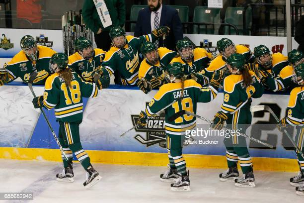 Cayley Mercer Loren Gabel and Genevive Bannon of the Clarkson Golden Knights of the Clarkson Golden Knights celebrate are congratulated by teammates...