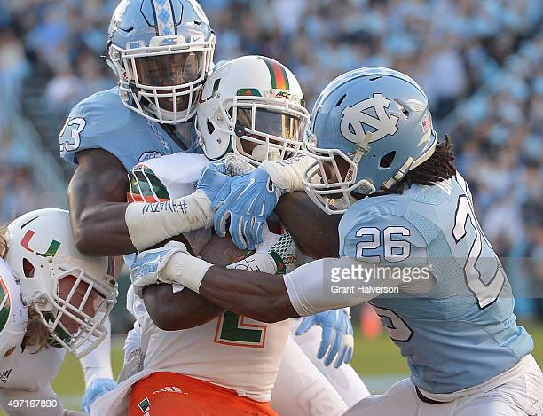 Cayson Collins and Dominquie Green of the North Carolina Tar Heels tackle Joseph Yearby of the Miami Hurricanes during their game at Kenan Stadium on...
