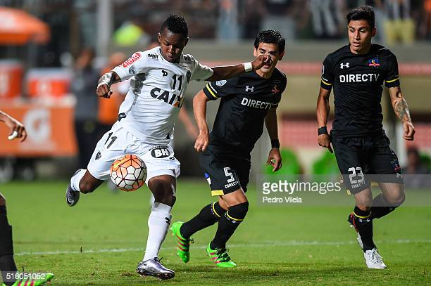 Cazares of Atletico MG and Julio Barroso and Claudio Baeza of Colo Colo battle for the ball during a match between Atletico MG and Colo Colo as part...