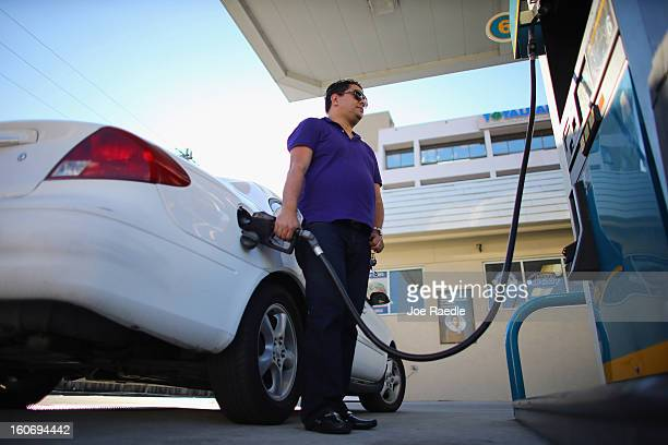 Ceasar Fernandez uses a gas station's pumps to fill his vehicle with gas on February 4 2013 in Miami Florida Reports indicate that gas pump prices...