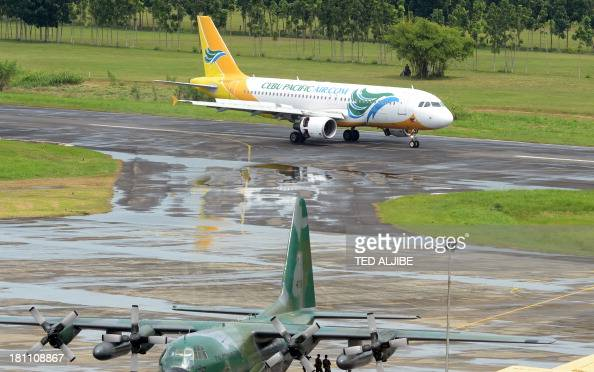 A Cebu pacific air passenger plane taxiis past a military C130 plane after landing at the airport for the first time since flights to and from the...