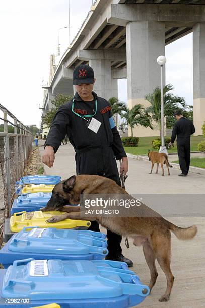 Troopers with bomb sniffing dogs check rubbish bins under a bridge 12 January 2007 where Asian leaders and their convoys pass through for their...