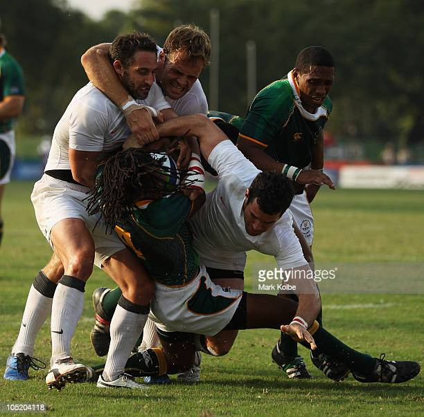 Cecil Africa of South Africa is tackled during the rugby 7's Bronze Medal match between England and South Africa at Delhi University during day nine...