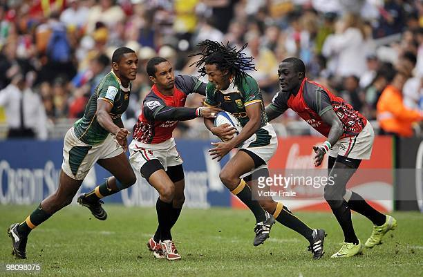 Cecil Afrika of South Africa eludes the Kenya defence on day three of the IRB Hong Kong Sevens on March 28 2010 in Hong Kong