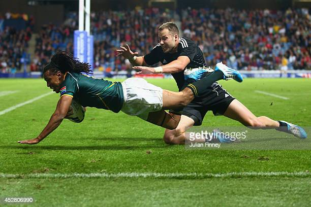 Cecil Afrika of South Africa jumps to score a try during the final match between South Africa and New Zealand at Ibrox Stadium during day four of the...