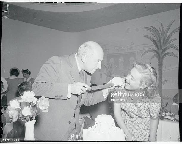 Cecil B Demille is shown offering a piece of his birthday cake to star Madeleine Carroll during the luncheon in honor of the Pioneer producer at the...