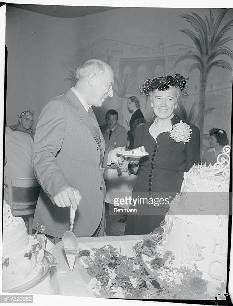 Cecil B DeMille who was honored by Hollywood screen celebrities on his 60th birthday cuts a piece of the cake for his wife They were to celebrate...