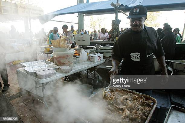 Cecil Palmer cooks Jamaican chicken for revelers during Mardi Gras festivities February 27 2006 in New Orleans Louisiana Palmer's home was heavily...