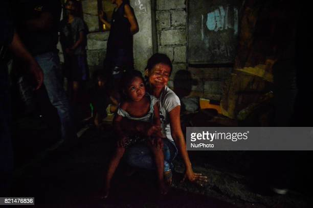 Cecile Santos weeps as she clutches her daughter near the scene where her husband Marvin De Los Santos was killed by unknown assailants in Quezon...