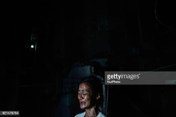 Cecile Santos weeps near the scene where her husband Marvin De Los Santos was killed by unknown assailants in Quezon city Metro Manila Philippines...