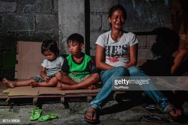 Cecile Santos weeps next to her children near the scene where her husband Marvin De Los Santos was killed by unknown assailants in Quezon city Metro...