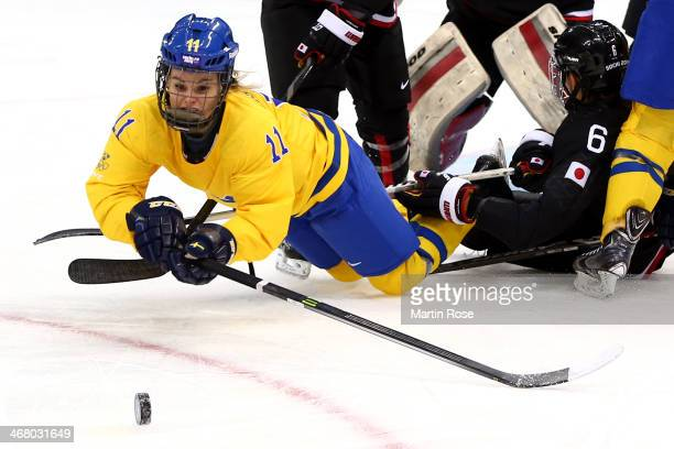 Cecilia Ostberg of Sweden tries to control the puck during the Women's Ice Hockey Preliminary Round Group B Game on day two of the Sochi 2014 Winter...