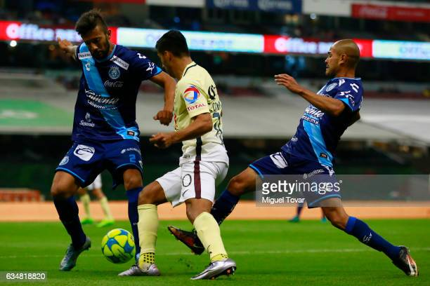 Cecilio Dom'inguez of America fights for the ball with Robert Herrera of Puebla during the 6th round match between America and Puebla as part of the...