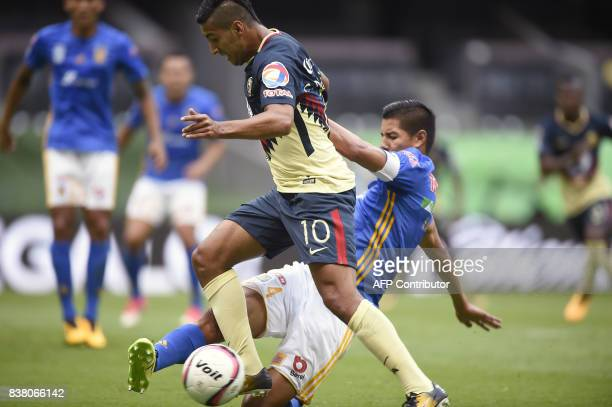 Cecilio Dominguez of America vies for the ball with Hugo Ayala of Tigres during their Mexican Apertura tournament football match at the Azteca...