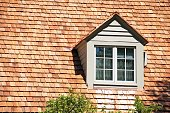 Dormer in roof of house with cedar shingles.