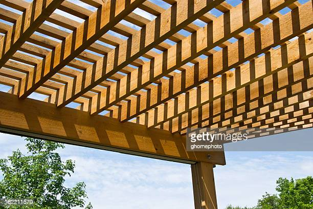 Cedar pergola with sky and trees in background