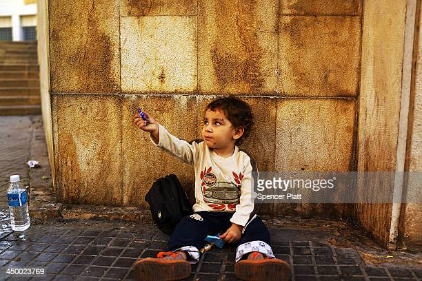 Cedra a Syrian boy from the city of Homs begs in a wealthy district of Beirut on November 16 2013 in Beirut Lebanon As the war in neighboring Syria...