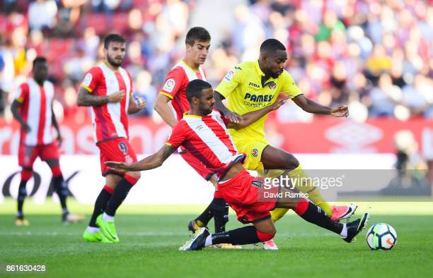 Cedric Bakambu of Villarreal CF competes for the ball with Jonas Ramalho of Girona FCduring the La Liga match between Girona and Villarreal at Estadi...