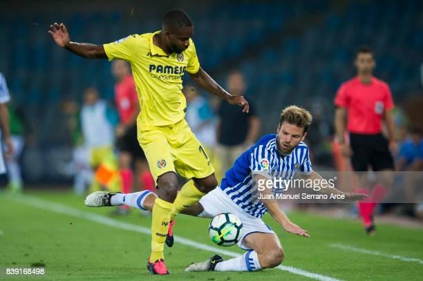 Cedric Bakambu of Villarreal CF duels for the ball with Asier Illarramendi of Real Sociedad during the La Liga match between Real Sociedad de Futbol...