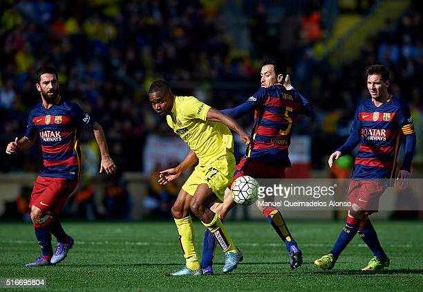 Cedric Bakambu of Villarreal is tackled by Sergio Busquets of Barcelona during the La Liga match between Villarreal CF and FC Barcelona at El...
