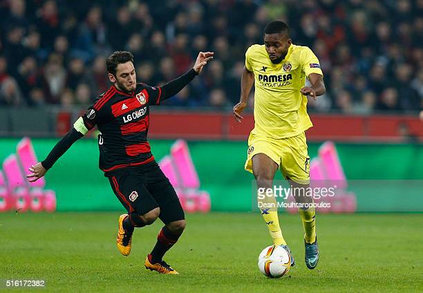 Cedric Bakambu of Villarreal takes on Hakan Calhanoglu of Bayer Leverkusen during the UEFA Europa League round of 16 second leg match between Bayer...